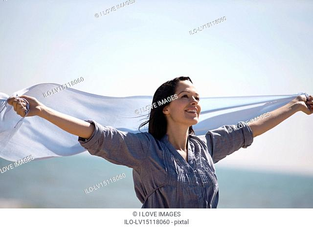 A pregnant woman on the beach, holding a scarf into the wind