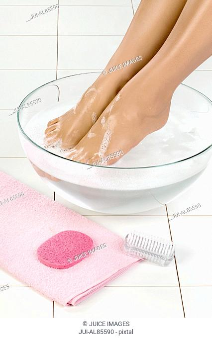 Close up of woman's bare feet in bowl of water next to pedicure items