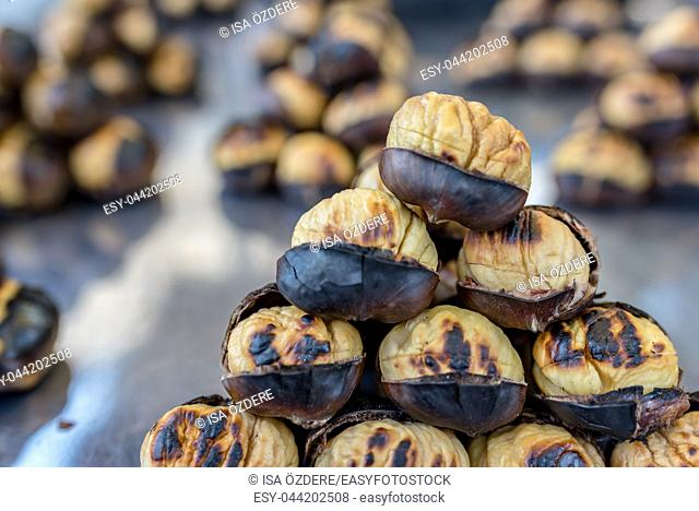 Close up view of baked chestnuts at a stand for selling at street
