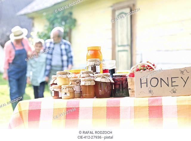 Grandparents and grandson walking toward honey stand
