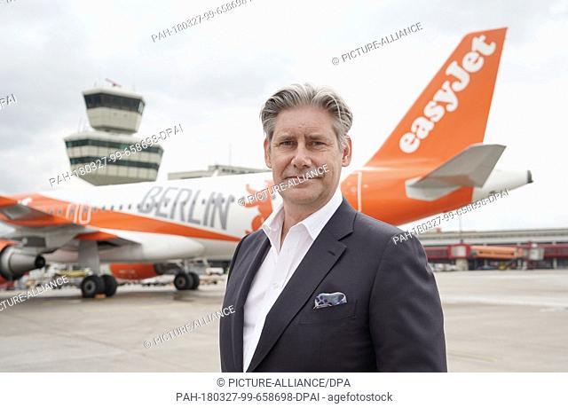 "dpatop - 27 March 2018, Germany, Berlin: Easyjet CEO Johan Lundgren standing in front of an Easyjet Airbus A320-214 in """"Berlin colours"""" in Berlin's Tegel..."