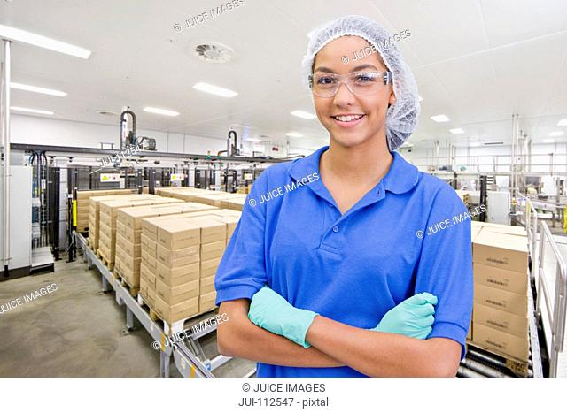 Portrait of smiling worker at food packaging production line