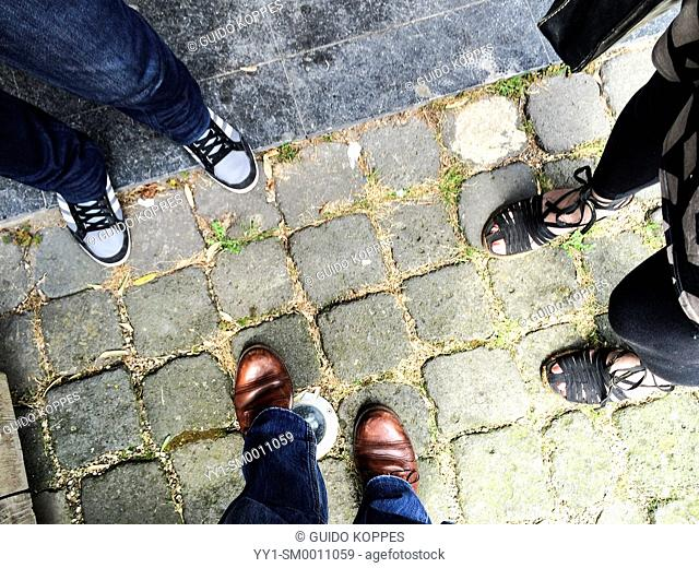 Amersfoort, Netherlands. Three pair of feed on the pavement of three people during a conversation