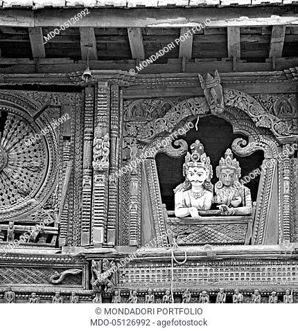 Two statues of gods looking out the window of a temple. Nepal, 1965