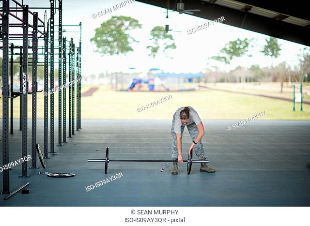 Female soldier preparing barbell at military air force base