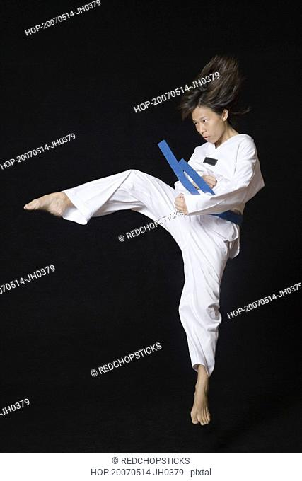 Young woman performing round kick