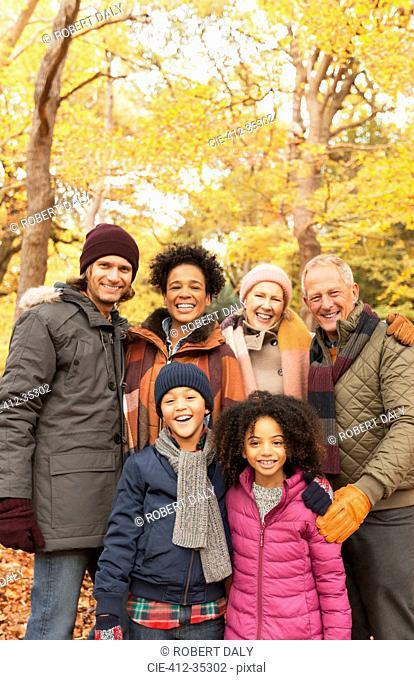 Portrait smiling multi-generation family in autumn woods