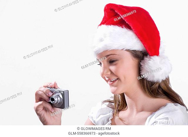 Teenage girl taking picture with a digital camera and smiling