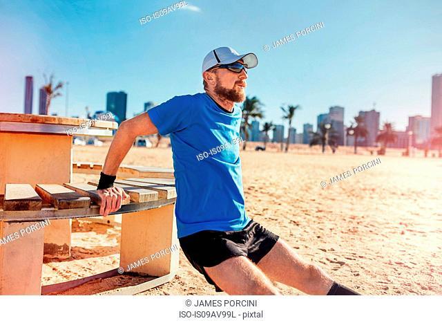 Mid adult man on beach doing reverse push up on bench, Dubai, United Arab Emirates