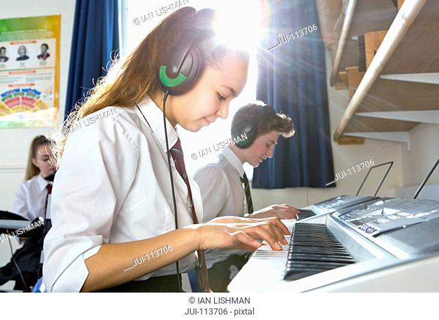 High school students with headphones playing piano in music class