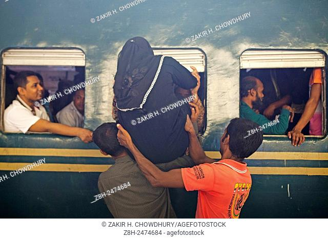DHAKA, BANGLADESH 16th July : Bangladeshi Muslims make space for themselves inside the overcrowded train to head home ahead of Eid al-Fitr as others wait at a...