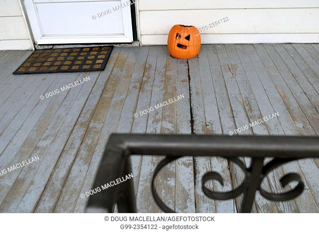 A Halloween pumpkin decomposes on a front porch in a residential area near Ottawa Street in Windsor, Ontario, Canada