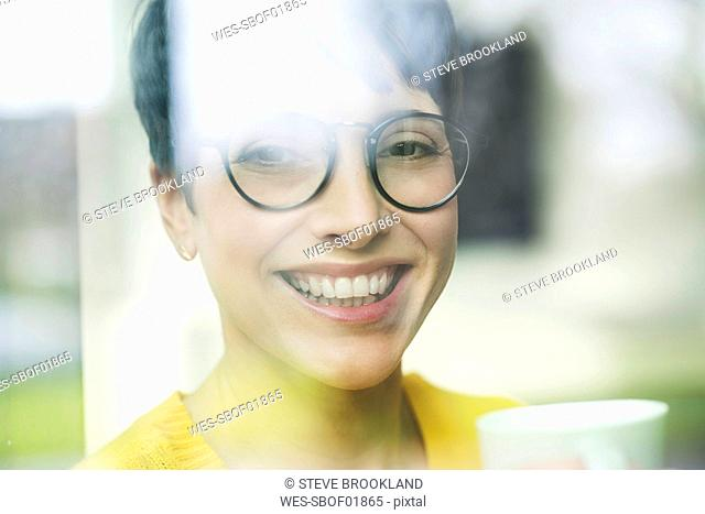 Portrait of laughing woman with cup of coffee behind windowpane