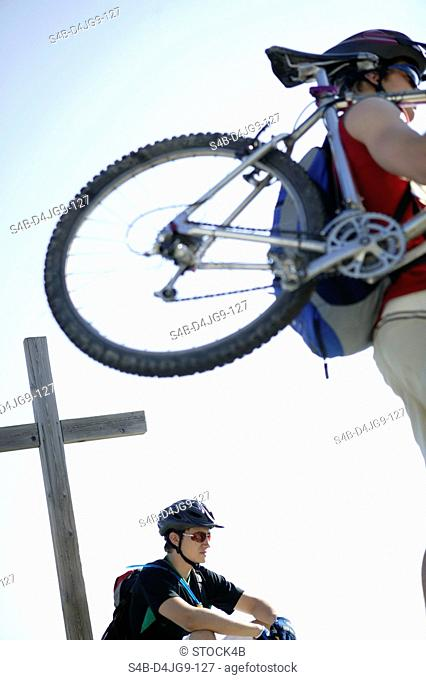 Person carrying a mountainbike whereas a man in sports clothing is sitting next to a wooden cross