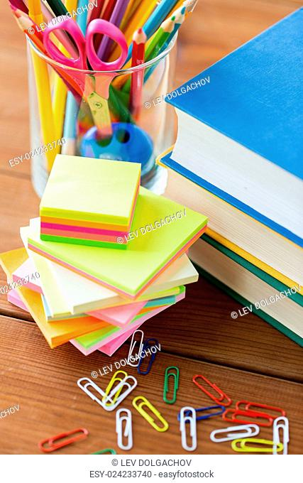 education, school supplies, stationery and object concept - close up of stand or glass with writing tools and book with scissors on wooden table