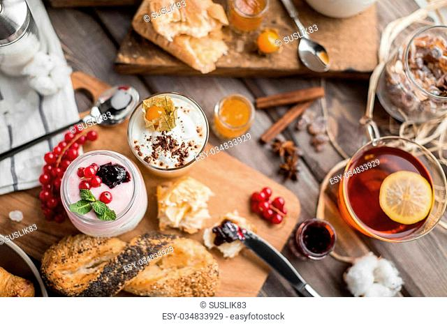 cream mousses and jams and buns and hot tea for a breakfast on a wooden table