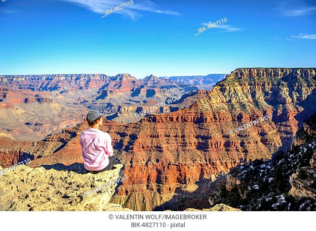 Young woman looking into the distance, sitting at the precipice of the gigantic gorge of the Grand Canyon, view from the Rim Trail