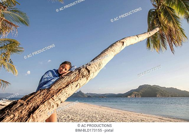Asian woman on palm tree on beach