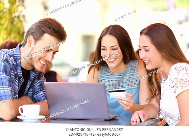 Three happy friends shopping online with a credit card and a laptop in a coffee shop