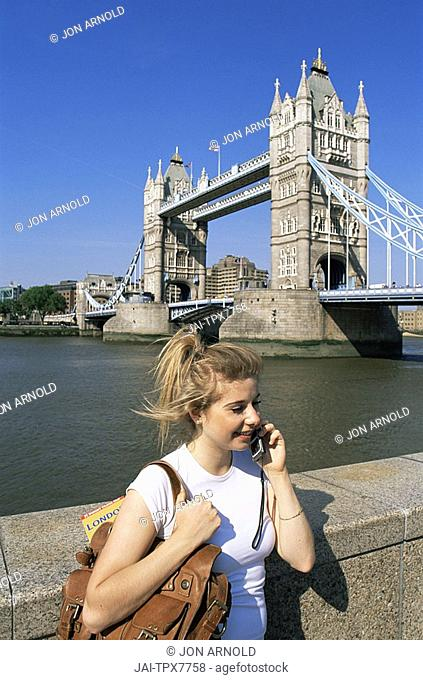 England,London,Female Tourist Talking on Moble Phone in front of Tower Bridge