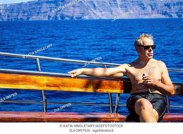 Very handsome caucasian retired man in his mid 60's with grey hair siting on the wooden bench of a Sailboat with his small camera in hands