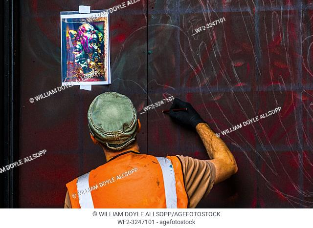 A graffiti artist laying out the basis for a new work