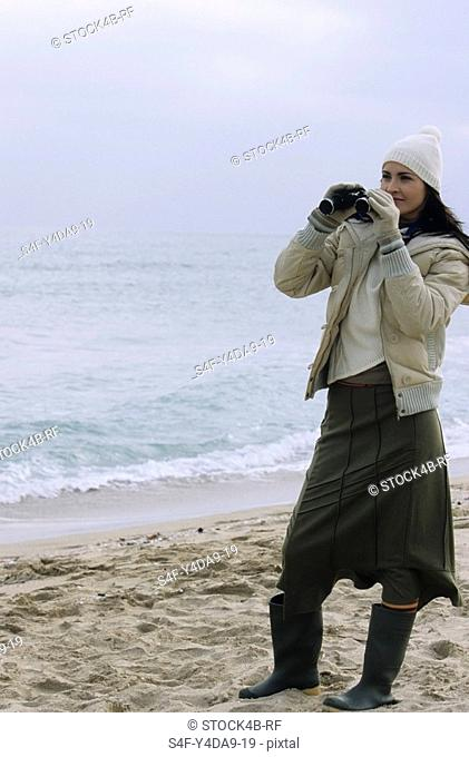 Young brownhaired Woman with woolen Hat and Rubber Boots looking through Binoculars - View - Leisure Time - Coldness - Beach