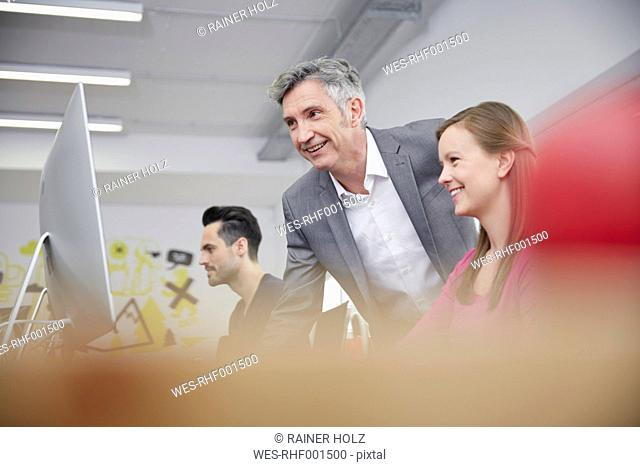 Mature businessman helping coworker