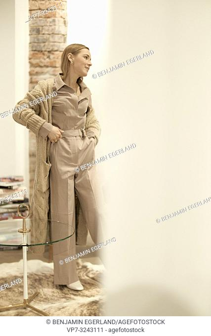 fashionable woman, wearing cool stylish one piece jumpsuit, beige trend outfit, women's fashion jumper, in Munich, Germany
