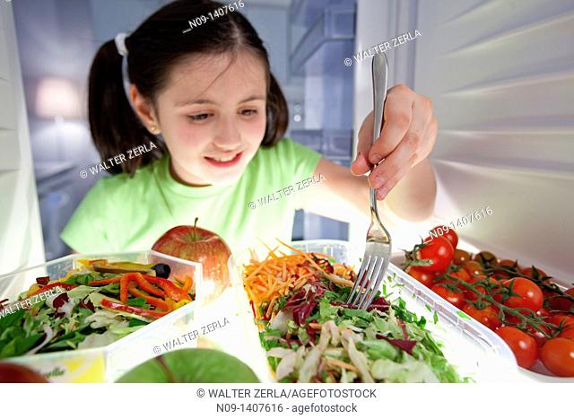 Girl eats salad from the fridge