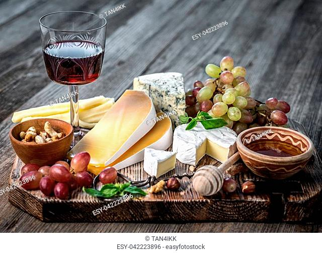 Cheese plate served with wine, nuts and honey top view