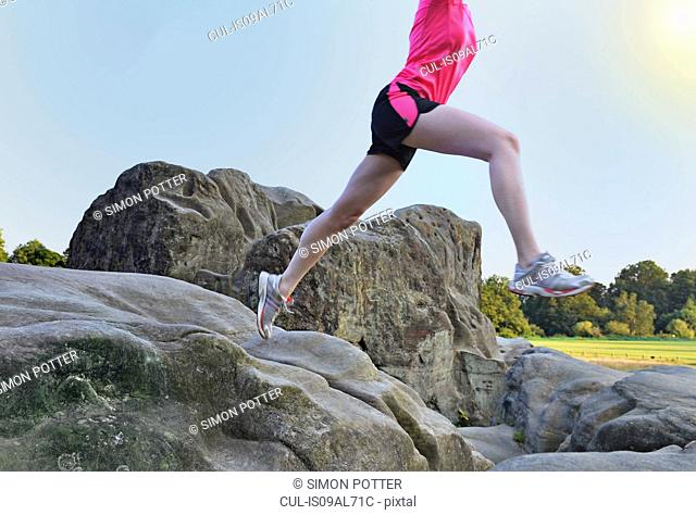 Neck down view of young female runner jumping over rock formation