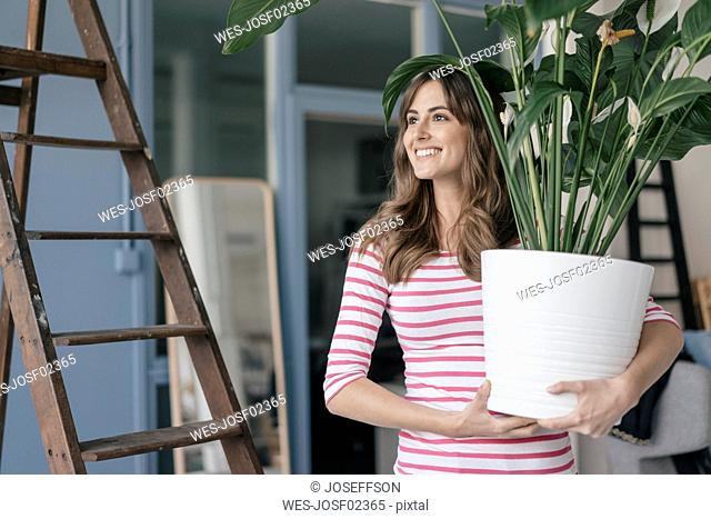 Woman holding potted plant in her bew home