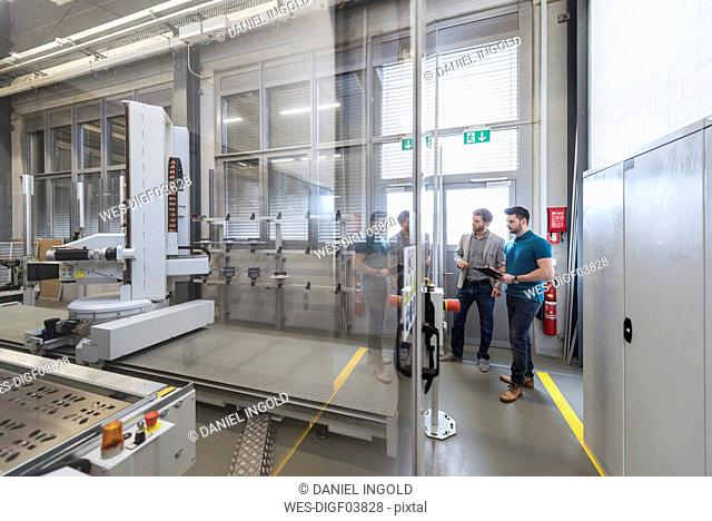 Two men looking at machine in modern factory