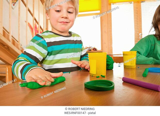 Germany, Two boys 3-4, 6-7 playing with modeling clay, portrait