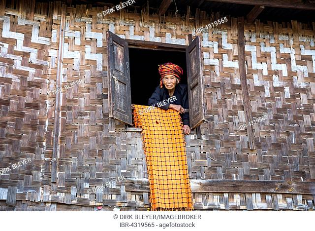 Old woman looking out of a lodge window, mountain tribe or mountain people of the Pa-O or Pa-Oh or Pao or Black Karen or Taungthu or dew-soo, ethnic minority