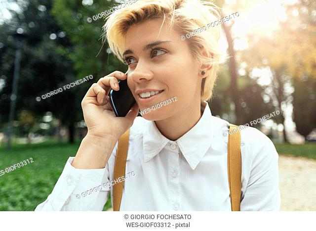 Blond teenage girl using smartphone in a park