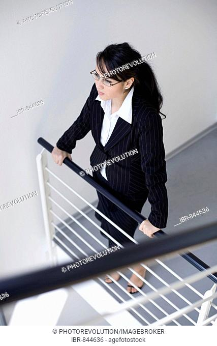 Dark-haired businesswoman wearing business-clothes, holding onto a railing, looking into the distance