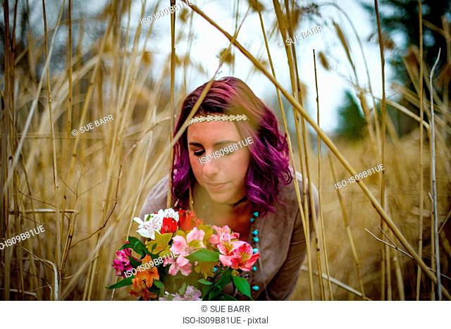 Woman with flowers among tall grass