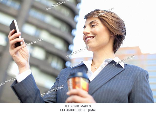 Businesswoman using cell phone outdoors