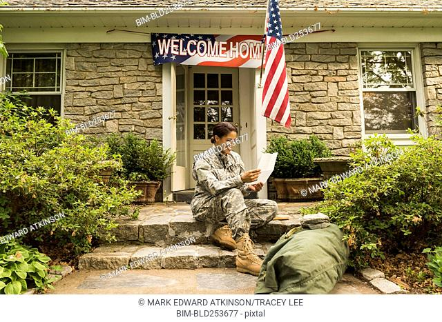 Smiling African American soldier sitting on front stoop reading letter