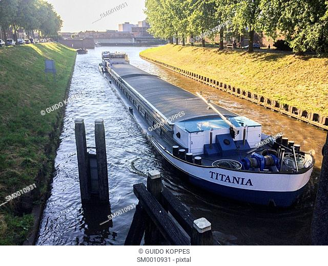 Den Bosch, 's-Hertogenbosch, Netherlands. Inland barge ship sailing and navigating through a narrow channel down town Den Bosch