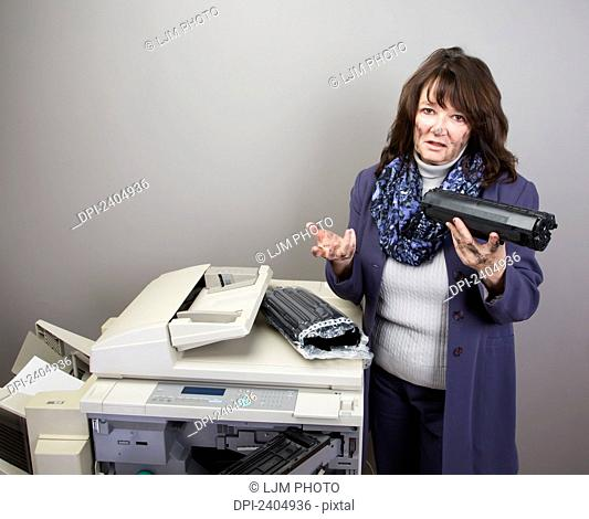 Office worker trying to replace a toner cartridge in a photocopier; Edmonton, Alberta, Canada