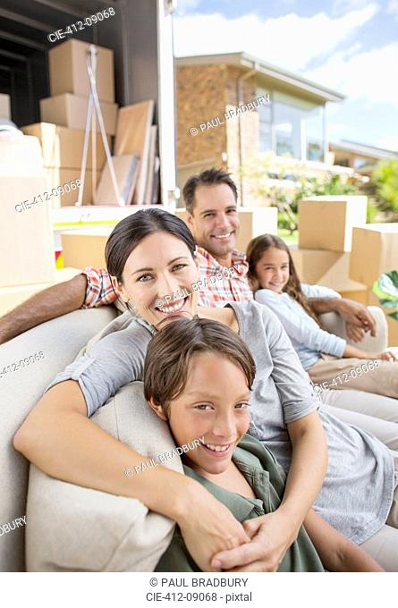 Family sitting on sofa near moving van in driveway