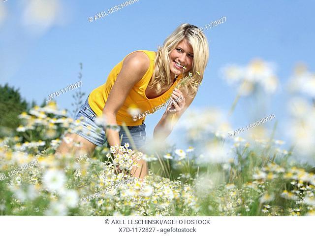 blond woman walking through fields picking wild flowers