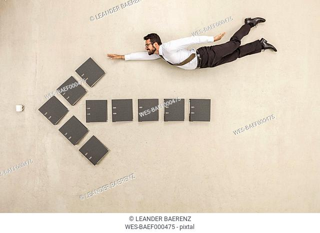 Businessman flying above files forming arrow sign