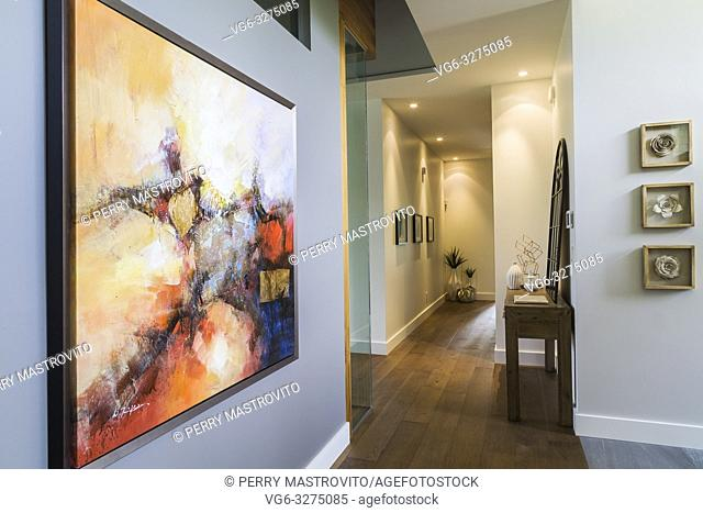 Framed abstract painting on grey wall of hallway with hickory wood floorboards inside a luxurious contemporary bungalow style home