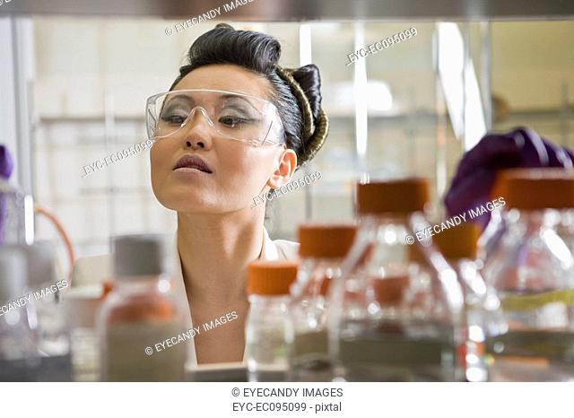 Young woman holding test tube tray