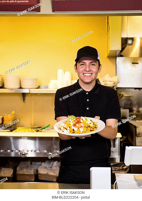 Hispanic server holding food in cafe