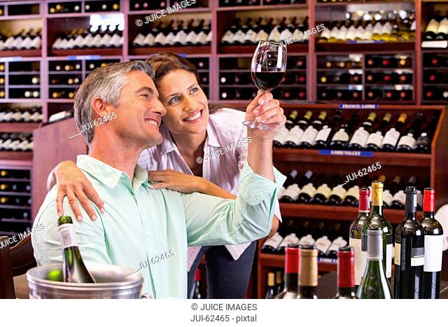 Curious couple examining glass of red wine in wine shop